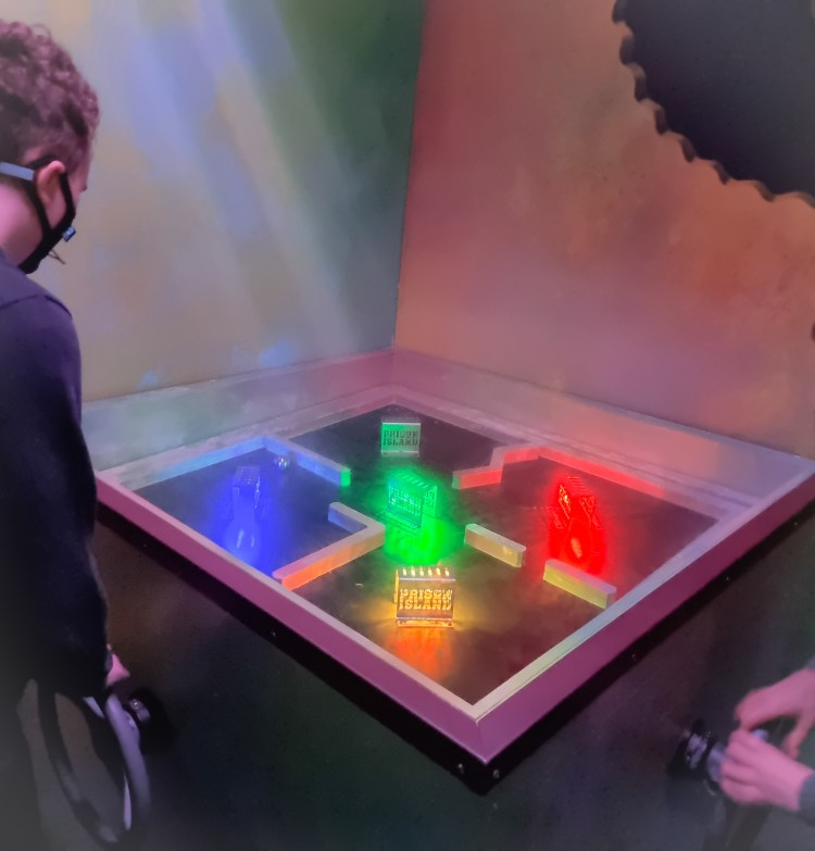 Prison Island Belfast. A series of rooms filled with challenges to try and score points. Rolling a ball through lit up tunnels.