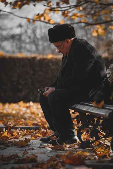 photo of man sitting on wooden bench while using cellphone
