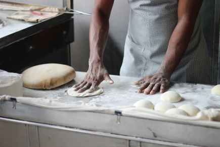 man preparing dough for bread
