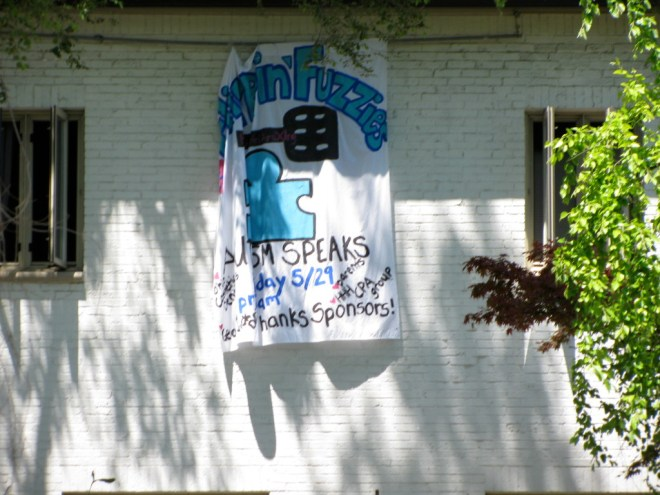 "A bit hard to read because of the wind, but the banner is hanging from a sorority house. It has a puzzle piece and Autism Speaks written on it, and is hanging for a fundraiser called ""flippin fuzzies."""