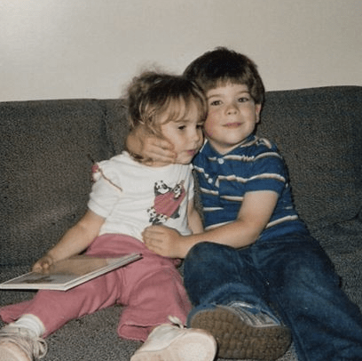 A girl toddler with a book is being hugged by a boy toddler. The girl is younger and is looking away from the camera, while the boy is smiling, looking toward the camera, and pushing the girl's face toward the camera.