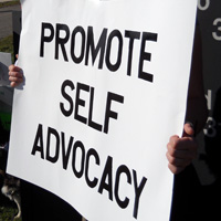 A protester holds a sign that reads PROMOTE SELF-ADVOCACY