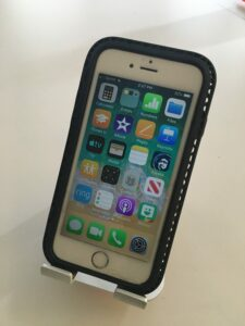 photograph of a small apple telephone with four columns across the top on its touch sensitive face with six rows down the bottom tilted to face the user with an aluminum support on a white desk.