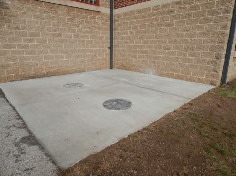 Concrete pad with manhold cover