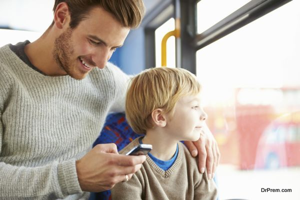 Father Using Mobile Phone On Bus Journey With Son