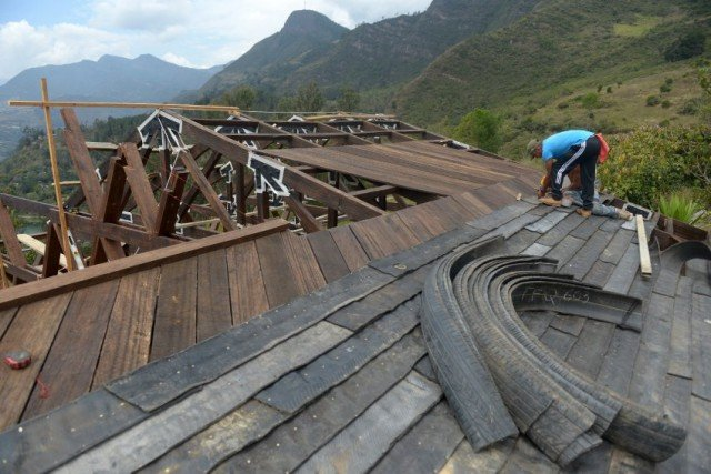 Men work building a house with tires in Choachi, Cundinamarca, Colombia on March 16, 2015. In the same way as igloos, thermally efficient and resistant to quakes, a particular kind of house in central Colombia takes advantage of a material which is thrown away: tires. 5.3 million tires are thrown away each year in Colombia, and since they take millions of years in decomposing, using them for building becomes a potential.  AFP PHOTO/Eitan Abramovich