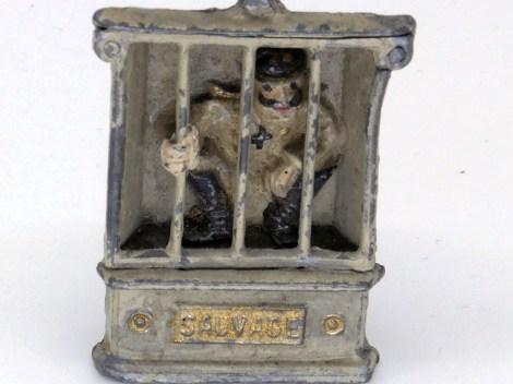 """figurine de Guillaume II dans sa cage avec la pancarte """"sauvage"""" et la colombe de la paix au-dessus"""