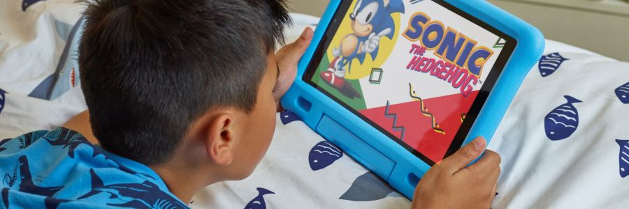 Child holding Fire HD 10 Kids Edition Tablet on bed