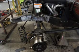 Freshly rebuilt front axle assembly with coil spring mount welded to the frame.