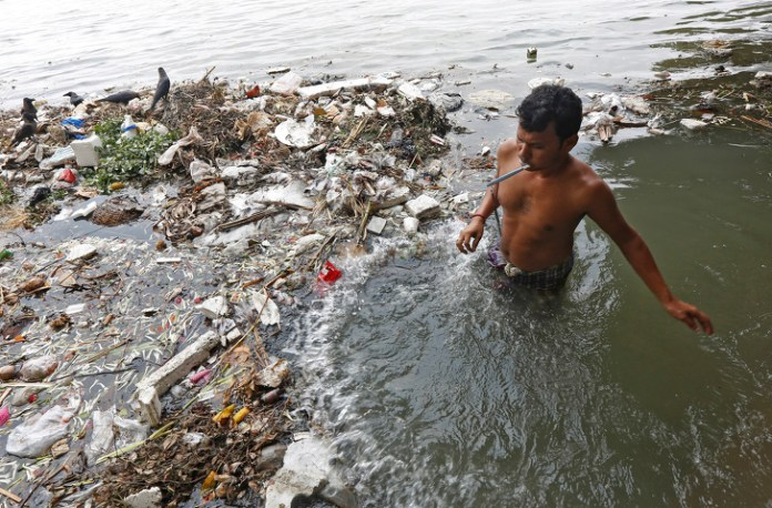 A man brushes his teeth as he stands in the polluted water of river Ganga in Kolkata