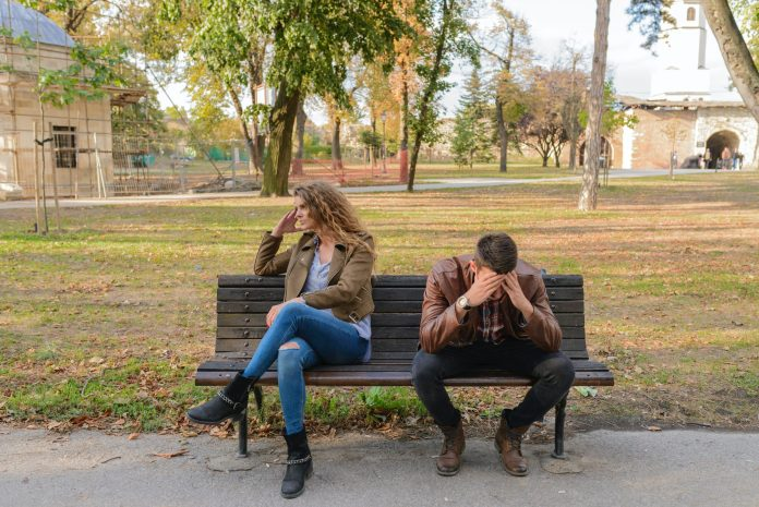 woman-and-man-sitting-on-brown-wooden-bench