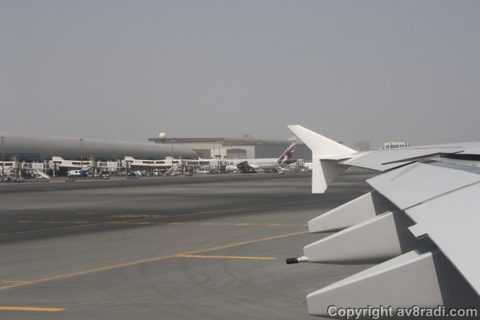 A Qatar Airways Boeing 777 parked at Terminal 1 and behind it is an Air Astana Boeing 757