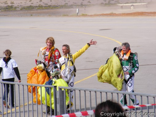 The 4 skydivers hug it out and wave at the cheering crowd