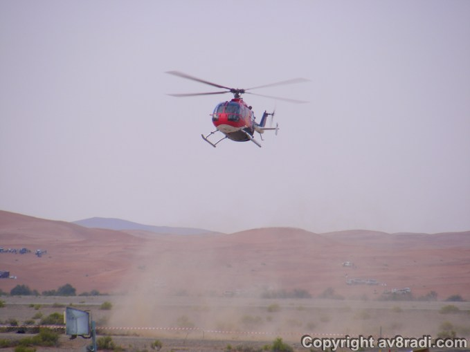 Red bull helicopter hovering in front of the crowd