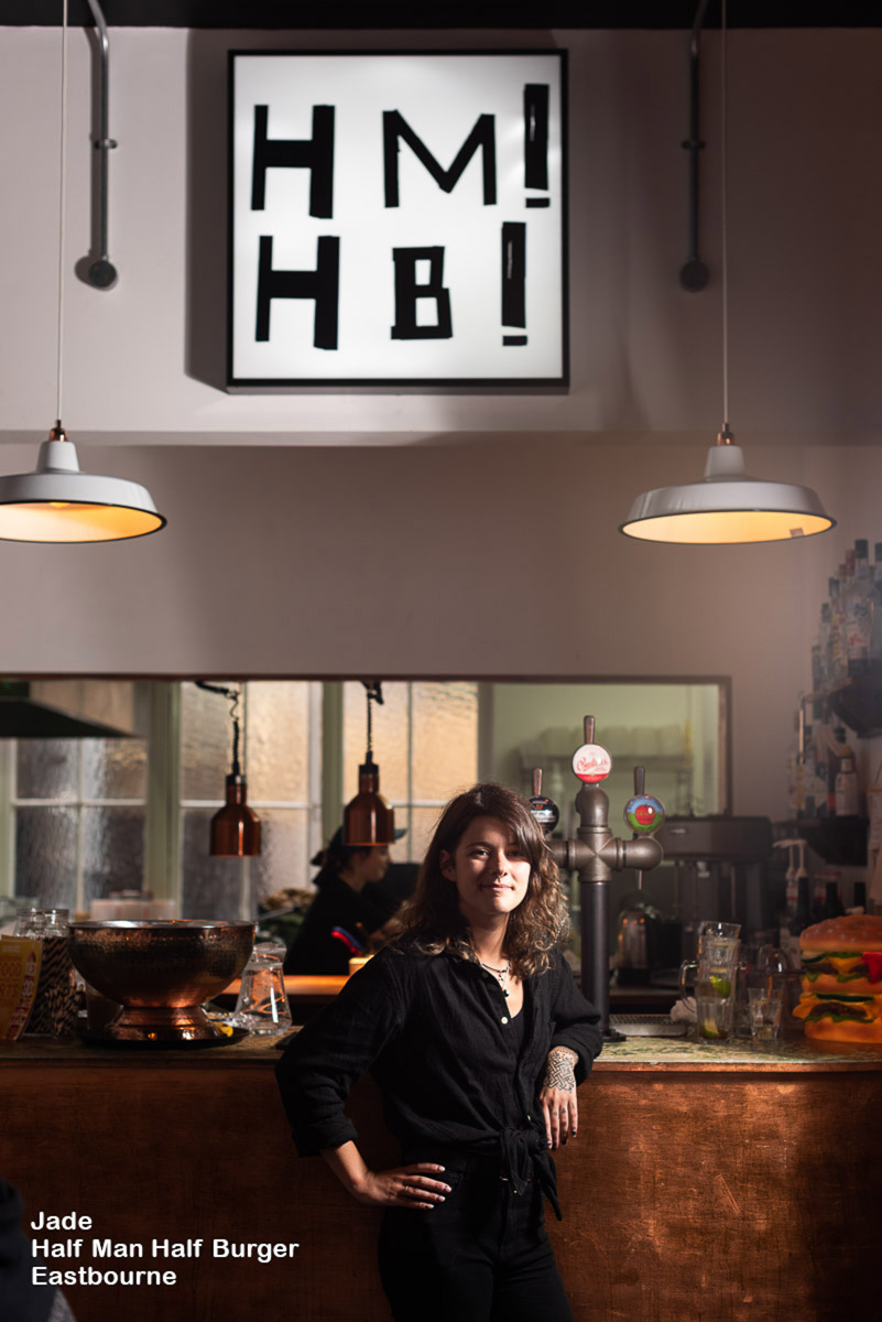 Young female server leans on bar at Half Man Half Burger restaurant