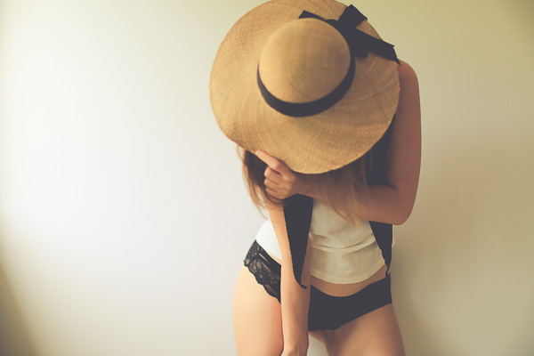 a sensual woman in a straw hat covering her face