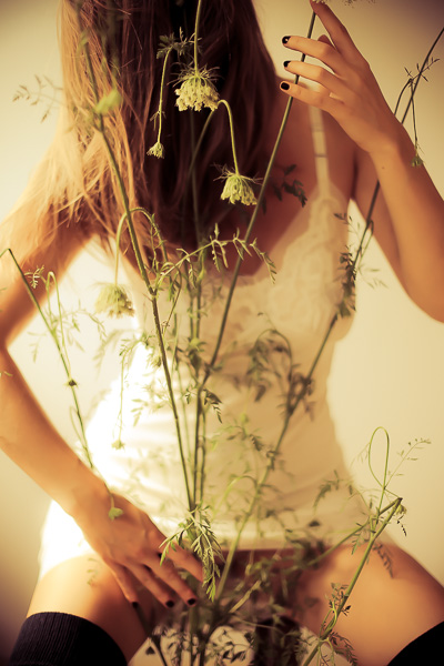 a sensual woman in a vintage slip pretending to play queen ann's lace like a cello