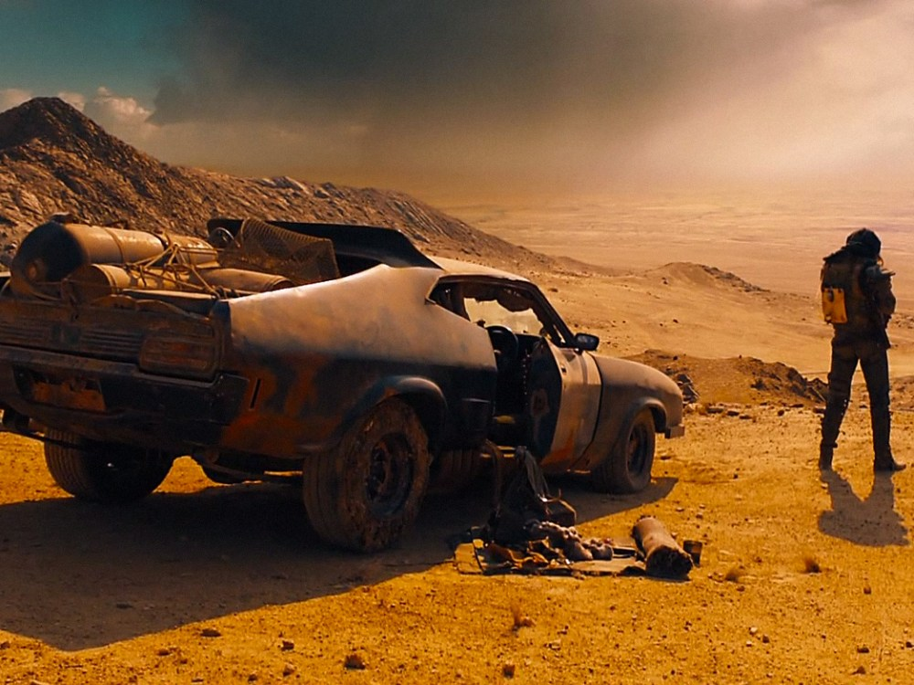 Mad Max with car. © Warner Bros. Pictures