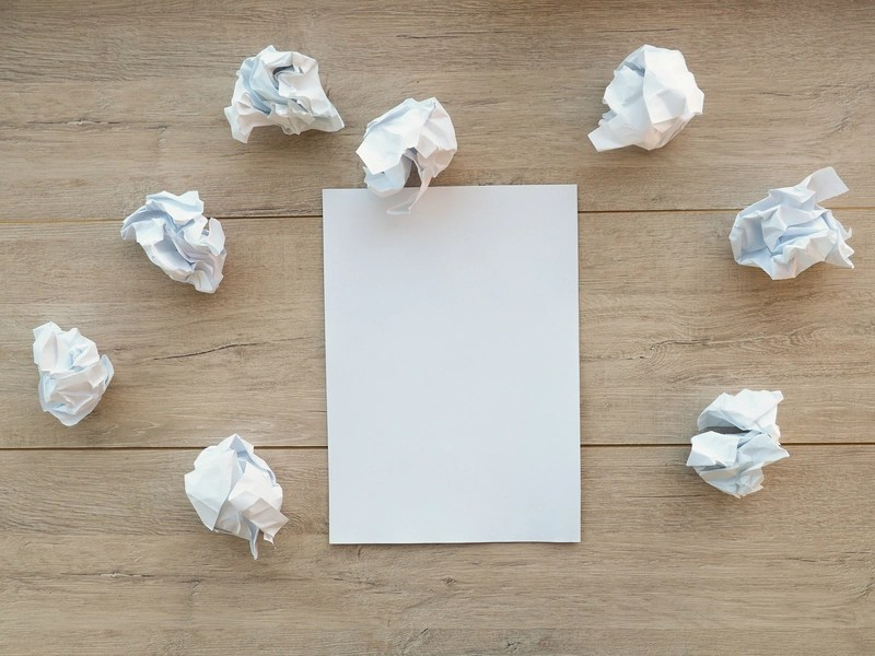Writing concept - crumpled up paper wads with a sheet of white paper
