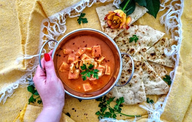 tofu makhani vegan with hand on bowl
