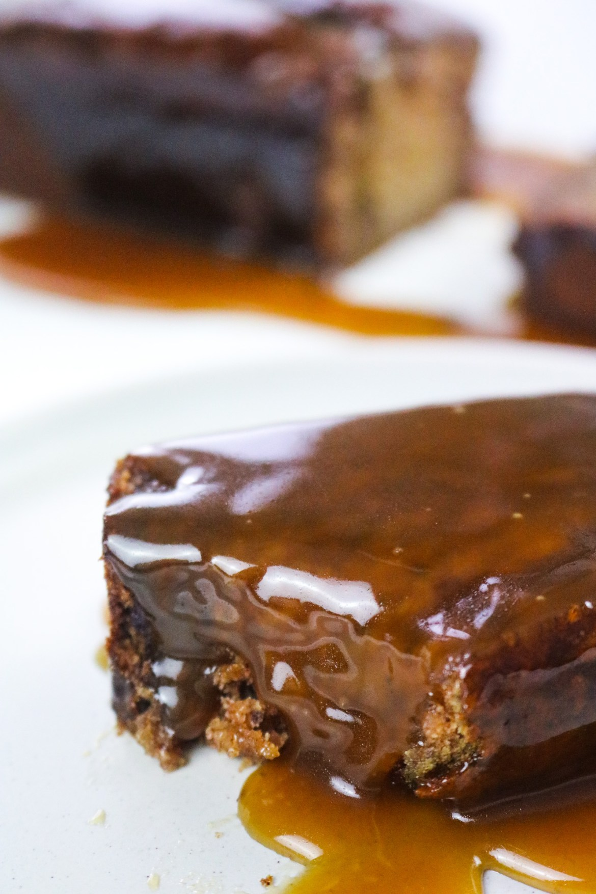 the best vegan sticky toffee pudding slice on a white plate covered in toffee sauce on focus and rest of loaf on the background