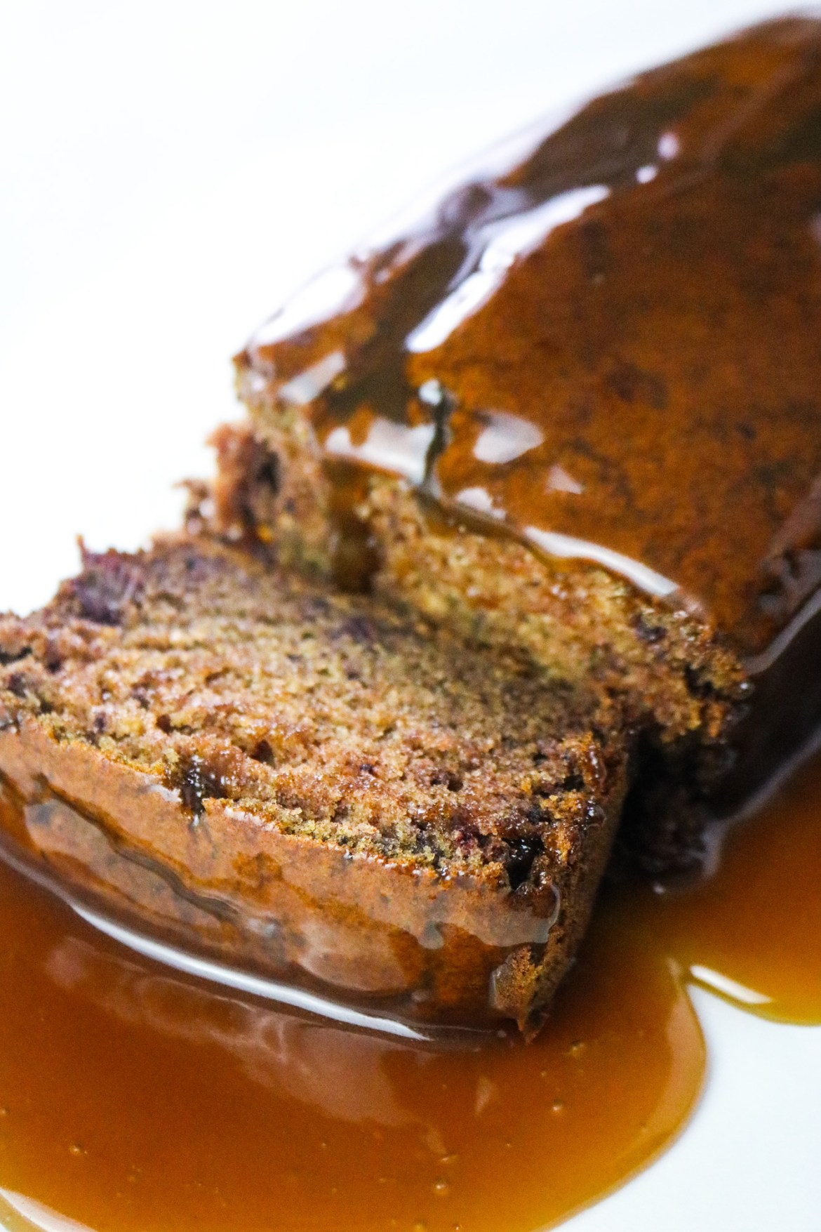 the best vegan sticky toffee pudding loaf on a white background with slice covered in toffee sauce on focus