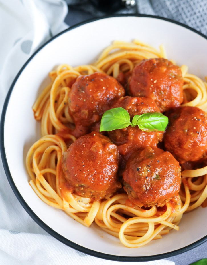 Close up of Lentil Meatballs in Rich Tomato Sauce over cooked spaghetti