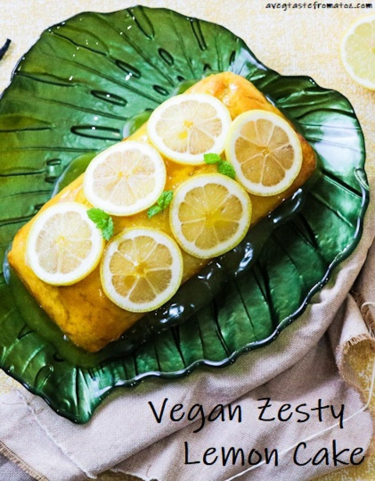 Lemon cake loaf on a green plate leaf shaped topped with lemon slices and mint
