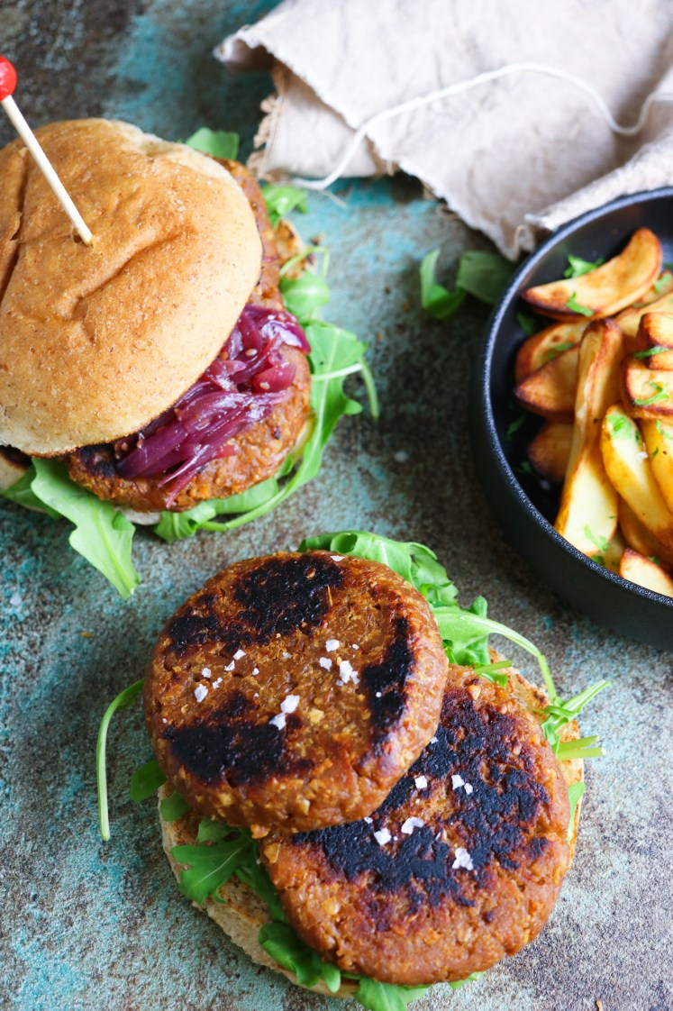 Vegan burgers patties made of soy TVP and gluten with oven baked chips on a side, ketchup and red onion chutney