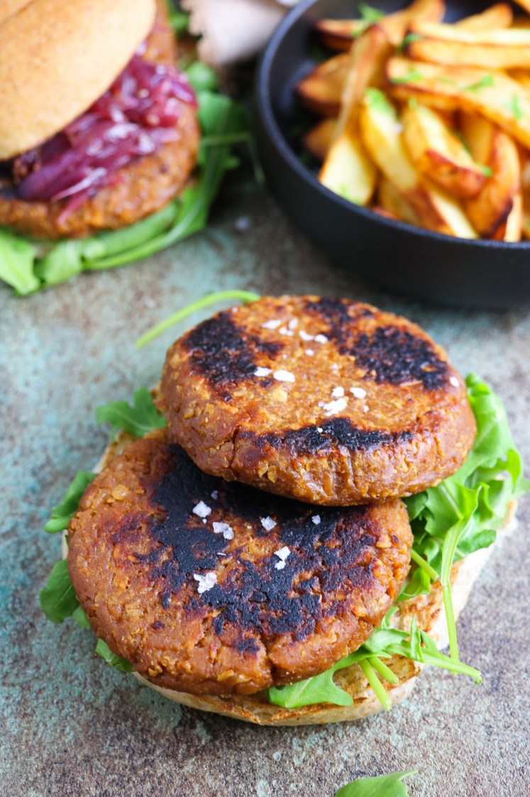 Vegan burgers patties made of soy TVP and gluten with oven baked chips on a side and a burger on the background