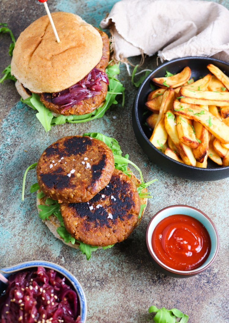Vegan burgers patties made of soy TVP and gluten with oven baked chips on a side, ketchup and a burger on the background oozing red onion chutney