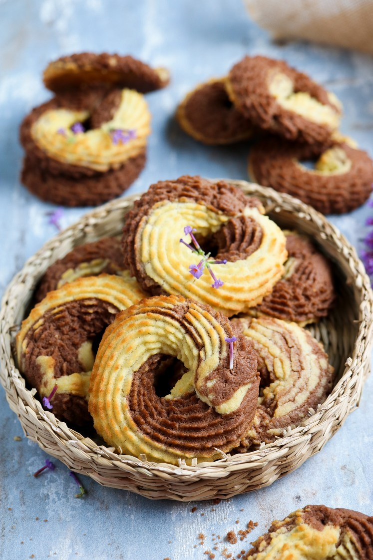 Vegan Whipped Cookies rings with cocoa powder nicely arranged on a wicker plate decorated with puple flowers