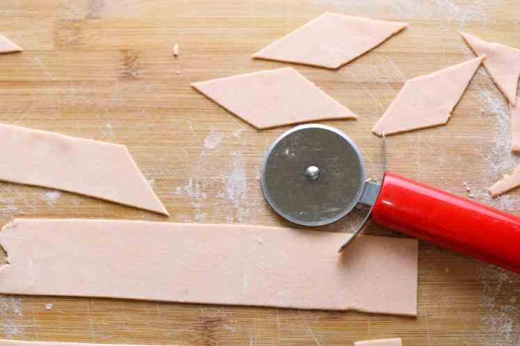 cutting red lentil pasta maltagliati with red pizza cutter
