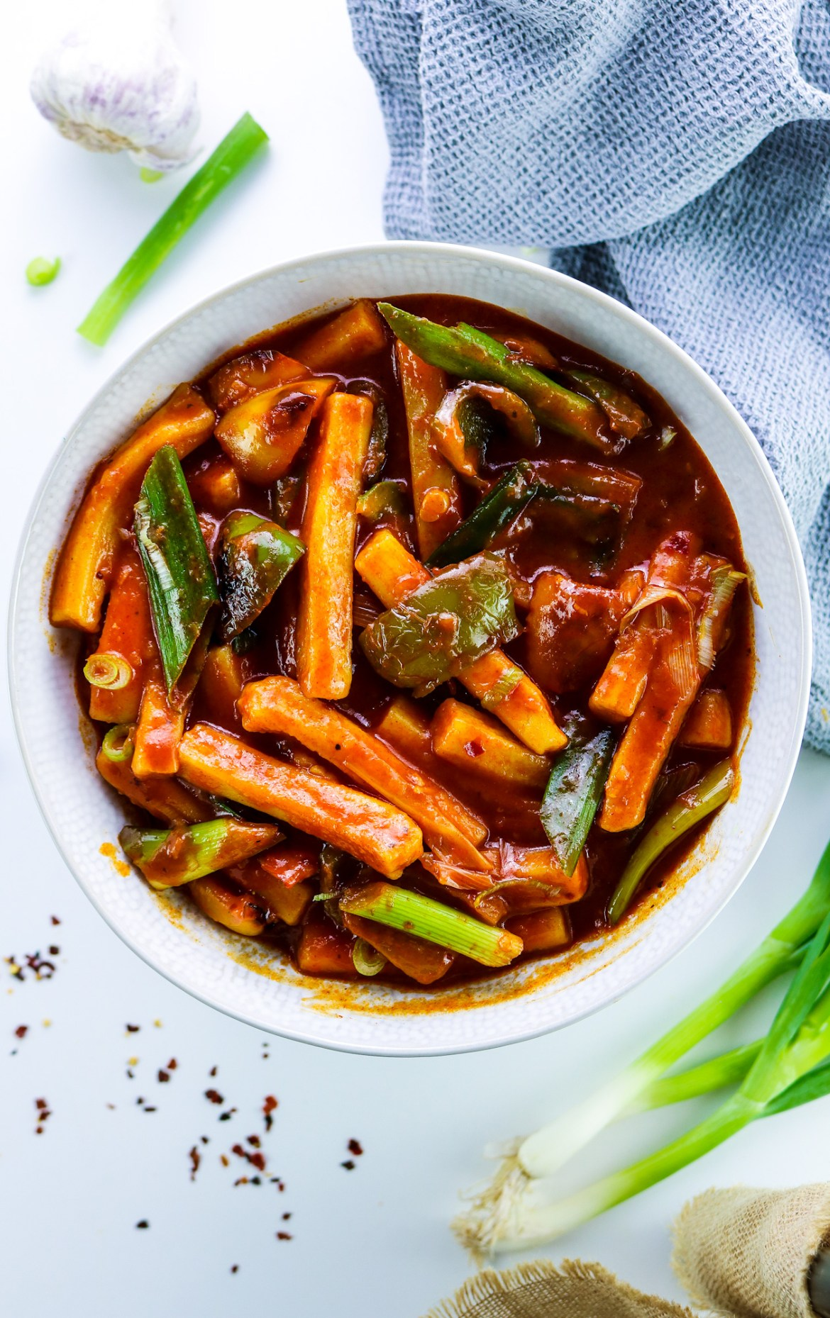 Korean Tteokbokki (떡볶이) with Peppers in a white bowl with white chinese spoon in the bowl, a bowl of kimchi in the corner, spring onions, a grey cloth, and fresh garlic around the dish