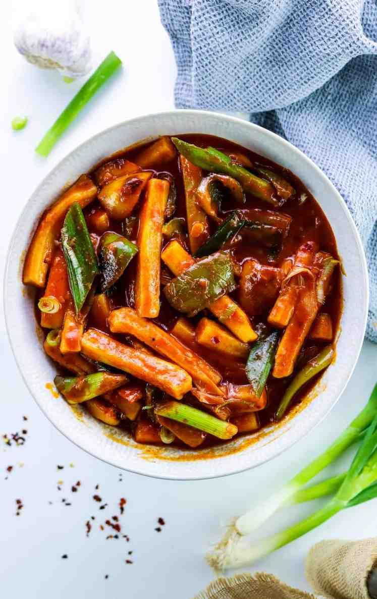 Piatto di Tteokbokki (떡볶이) Coreano con Peperoni con decorazioni di cipollotti, aglio fresco e peperoncino in polvere