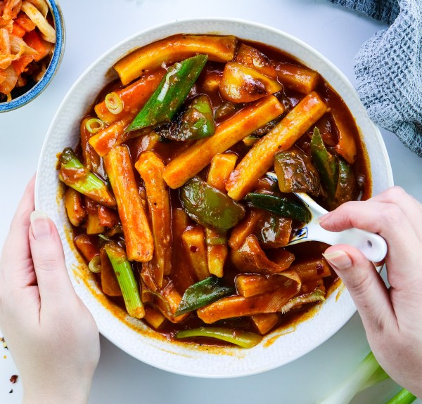 Korean Tteokbokki (떡볶이) with Peppers in a white bowl with white chinese spoon in the bowl, a bowl of kimchi in the corner, left hand holding the bowl and right hand stirring the dish with a chinese spoon