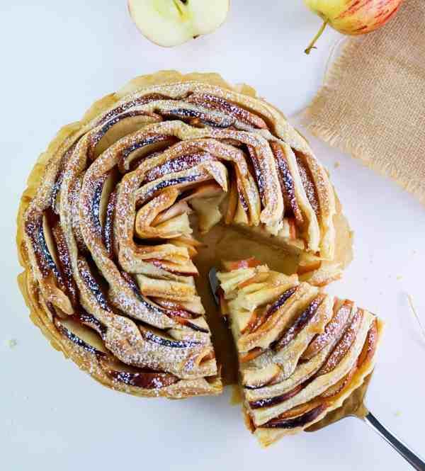 flaky apple tart with a slice on dessert spatula