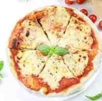 Pizza Margherita intera vegana tagliata in 6 fette con basilico fresco al centro su fondo bianco decorata con pomodorini maturi e foglie di basilico