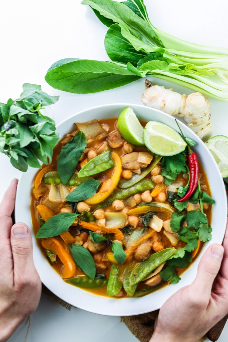 White ceramic bowl hold by both hands filled with rich vegan thai red curry with chickpeas, peppers, mangetout, thai basil, coriander leaves and lime wedges