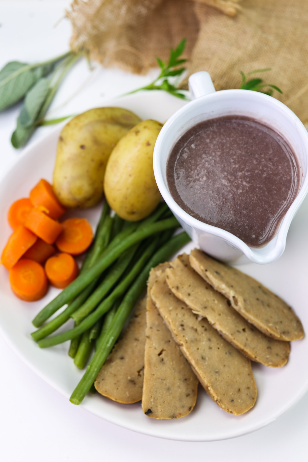 Turkey(less) roast, vegan and gluten free meat alternative sliced on a plate with steamed vegetables and gravy pot