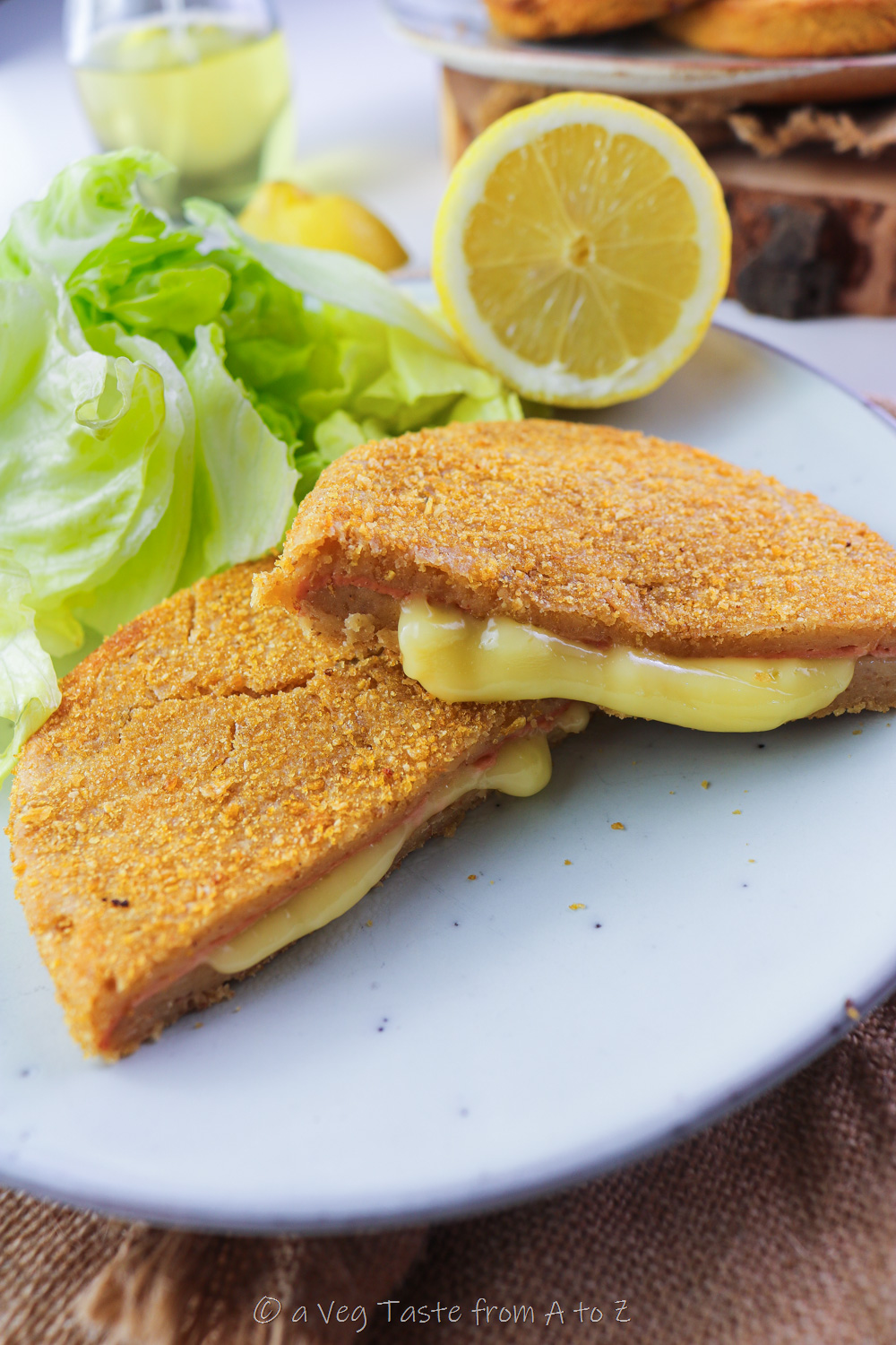 cordon bleu cut in half with oozy filling on a plate with salad and lemon close up