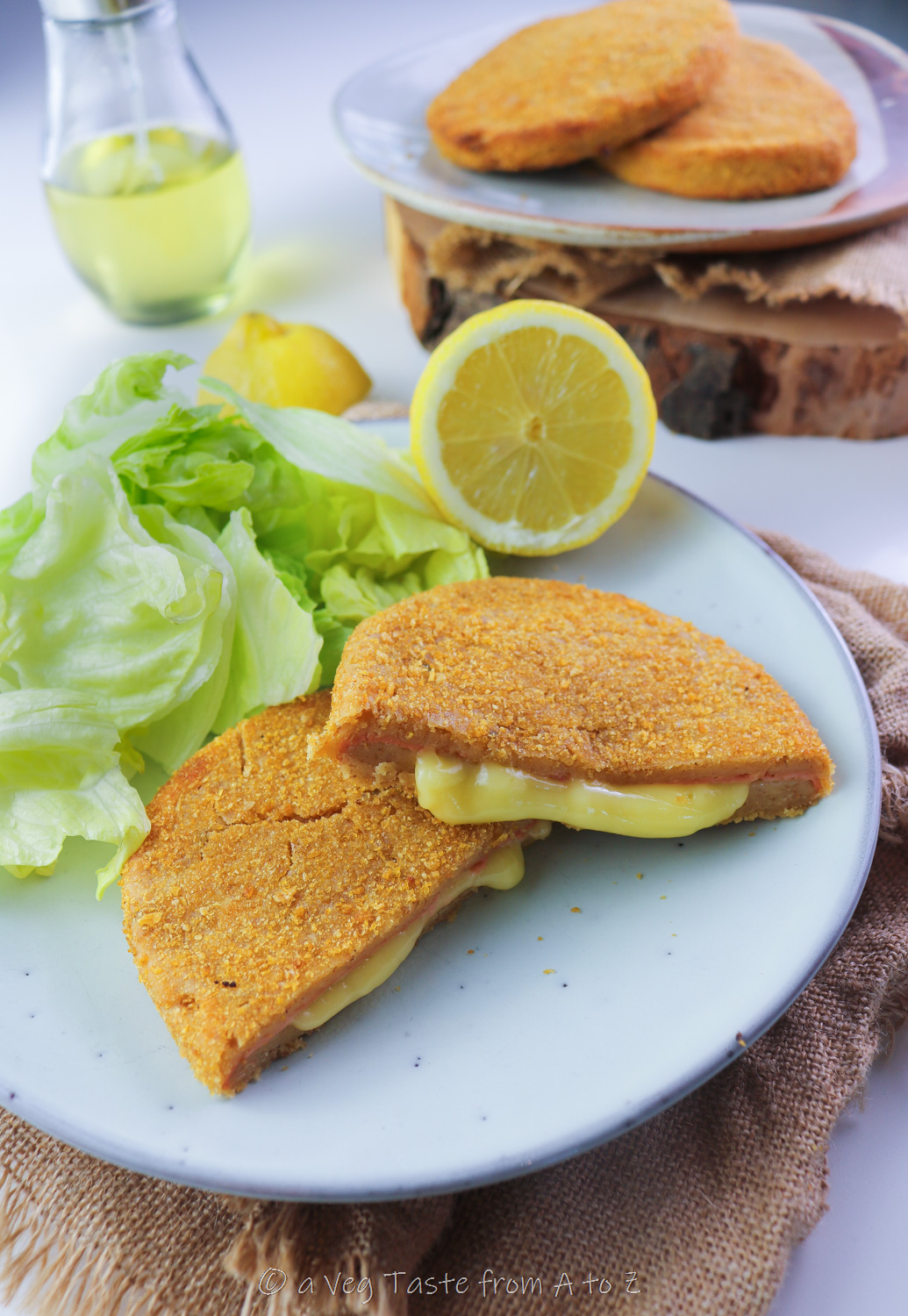cordon bleu cut in half with oozy filling on a plate with salad and lemon
