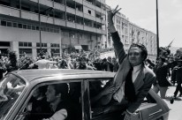 1974 - João Soares conduz o pai Mário que salta da janela do carro, acenando aos populares [EXPRESSO]