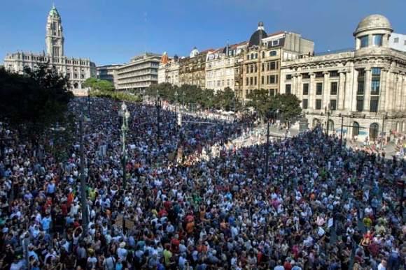 """Participantes da manifestação """"Que se lixe a troika! Queremos as nossas vidas!"""", que surgiu na Internet, através das redes sociais, empunham cartazes e gritam palavras de ordem contra as medidas de austeridade anunciadas pelo Governo, no Porto, 15 de setembro de 2012. Mais de 50 mil pessoas são esperadas hoje, em Lisboa, na manifestação contra as medidas de austeridade anunciadas pelo Governo, num protesto que também vai decorrer noutras 40 cidades portuguesas. PEDRO GRANADEIRO / LUSA"""