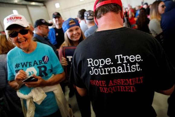 "A man wears a shirt reading ""Rope. Tree. Journalist."" as supporters gather to rally with Republican presidential nominee Donald Trump in a cargo hangar at Minneapolis Saint Paul International Airport in Minneapolis, Minnesota, U.S. November 6, 2016. REUTERS/Jonathan Ernst     TPX IMAGES OF THE DAY"