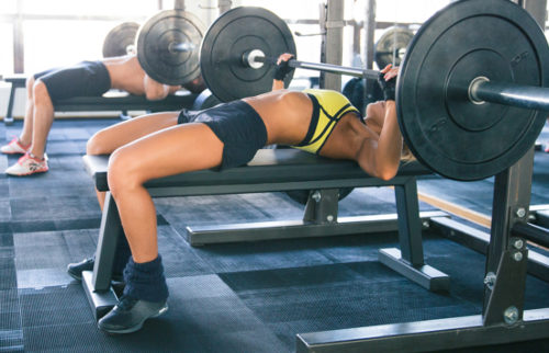Woman and man workout with barbell on bench at gym
