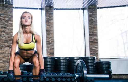 Woman workout with barbell and coach at gym