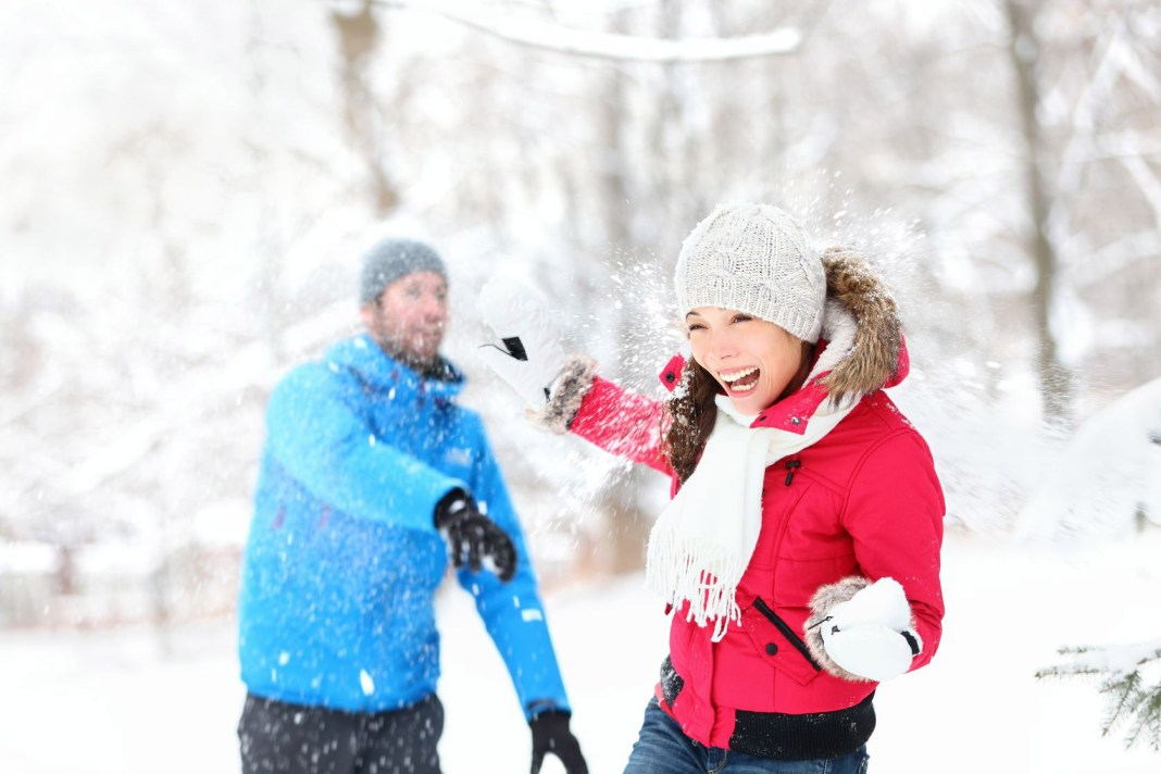 Couple playing snow ball fight in the snow