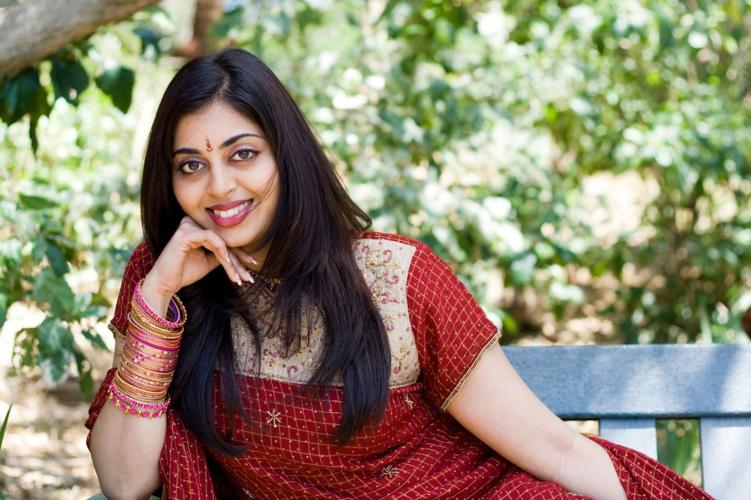 beautiful indian woman sitting on bench smiling