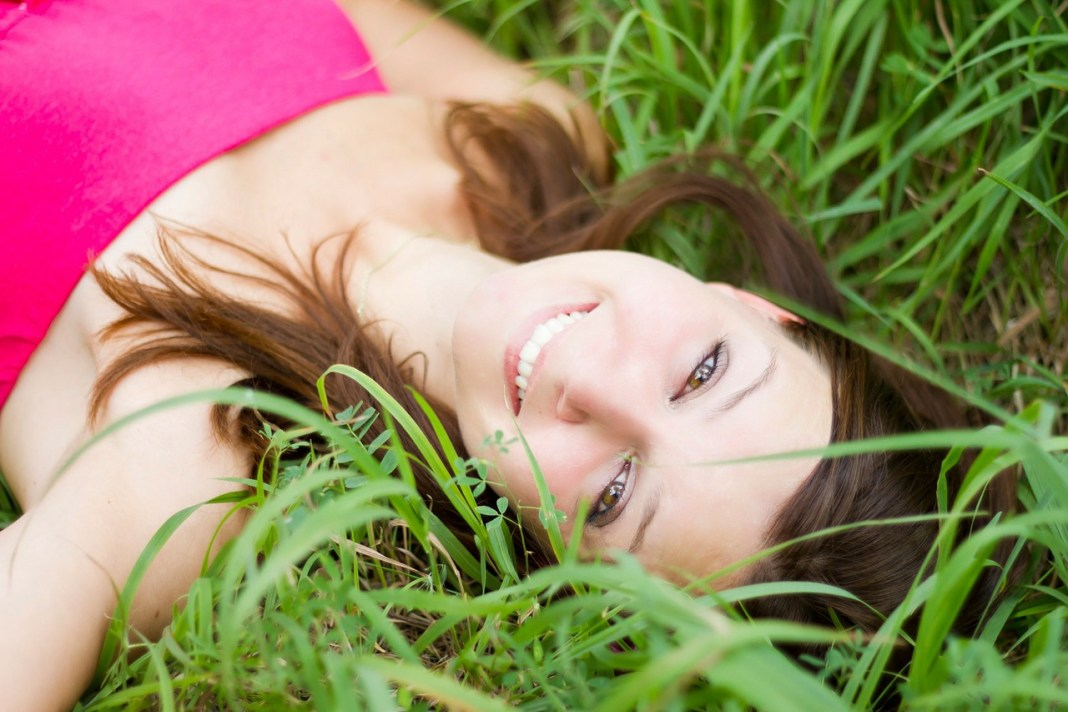woman-lying-in-grass-smiling
